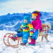 Kids having fun on a sleigh ride in snow — Stock Photo #82276762