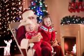 Kids and Santa at fire place on Christmas eve — Stock Photo