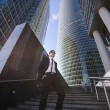 Businessman standing on a ladder, surrounded by skyscrapers. — Stock Photo #67222651