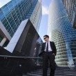 Businessman standing on a ladder, surrounded by skyscrapers. — Stock Photo #67222667