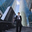 Businessman standing on a ladder, surrounded by skyscrapers. — Stock Photo #67222679