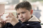 Boy kid child playing with mobile phone — Stock Photo