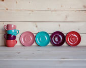 Colorful coffee cups over obsolete grunge wooden background — Stock Photo