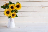Sunflowers in a vase on a rustic, gray background — Stock Photo