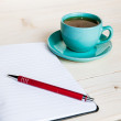 Open a blank white notebook, pen and cup of tea on the desk — Stockfoto #54167713