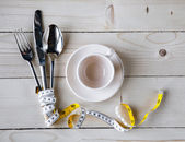 Empty plate, cup with measure tape, knife and fork. Diet food on wooden table — Photo
