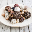 Decorative twig spheres lay in wooden bowl on wooden table — Stock Photo #55375543