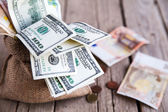 Money in sackcloth and coins scattered on a wooden background — Stock Photo