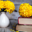 Flowers. Beautiful yellow chrysanthemum in a vintage vase. Cup of coffee. Bright Servais, cup and saucer .. Beautiful breakfast.Old books on a wooden background. — Stock Photo #58663457