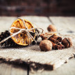 Dried orange tied with pine cones and nuts on a wooden backgroun — Stock Photo #63739435