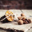 Dried orange tied with pine cones and nuts on a wooden background — Stock Photo #63739553