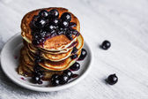Picture of few pancakes with blackberries and sugar on wooden background — Stock Photo