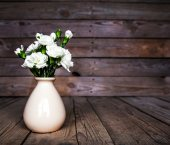 Delicate bouquet of carnations in vintage vase with heart on woo — Stock Photo