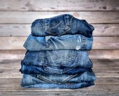 Fashionable clothes. pile of jeans on a wooden background — Stock Photo