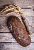 Rustic bread and wheat on an old vintage planked wood table. Dark moody background with free text space. — Stock Photo