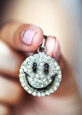 Pendant smile in female hands — Stock Photo