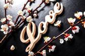 Цветут на черном фоне и деревянный знак с слово любовь — Стоковое фото