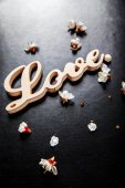 Bloom on a black background and a wooden sign with the word love — Stock Photo
