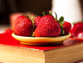 Strawberries on a red book in a yellow plate. fruit — Stockfoto