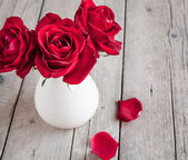 Red rose in vase on wooden table — Stock Photo