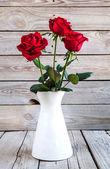 Rosa vermelha em vaso na mesa de madeira — Fotografia Stock