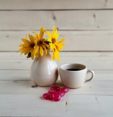 A beautiful arrangement of yellow flowers, sweets and cup of coffee — Stock Photo