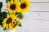 A bouquet of autumn sunflowers in a vase on a grungy wooden table. — Stock Photo