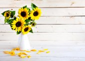 A bouquet of autumn sunflowers in a vase on a wooden table. — Stock Photo