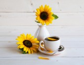 Sunflower and a cup of coffee on a wooden background — Stock Photo