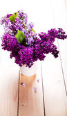Lilac Bouquet in ceramic jug against a white wooden wall. — Stock Photo