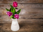 Vase of natural tulips. flowers on a wooden background — Stock Photo