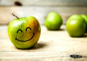 Fruit. fresh green apples on wooden background. with a smile on — Photo
