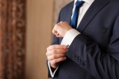 Closeup of a man in black suit correcting a sleeve — Stock Photo