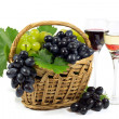 Fresh Red and White Grapes with Green Leaves in Wicker Basket and Two Wine Glass Cups Filled with Red and White Wine Isolated on White — Stock Photo #56648505