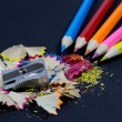 Sharpened Colorful Pencils Coming from Corner, Metallic Pencil Sharpener and Colorful Pencil Shavings on Black — Stock Photo #60641681