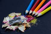 Sharpened Colorful Pencils Coming from Corner, Metallic Pencil Sharpener and Colorful Pencil Shavings on Black — Stock Photo