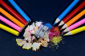 Sharpened Colorful Pencils Against Blunt Pencils with Metallic Pencil Sharpener and Colorful Pencil Shavings on Black — Stock Photo