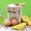 Pasta, Two Eggs, Jute Bag Filled with Flour, Wooden Spoon and Olive Oil in Glass Bottle on an Old Wooden Table — Stock Photo #64326355