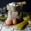 Pasta, Two Eggs, Jute Bag Filled with Flour, Wooden Spoon and Olive Oil in Glass Bottle on an Old Wooden Table — Stock Photo #64400347