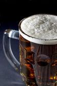 Mug of Fresh Beer with Foam Over Black Background — Stock Photo