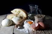 Stillleben mit Zutaten für Brotbacken auf Holztisch auf schwarzem Hintergrund — Stockfoto