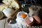 Dough, Loaf of Bread and Ingredients for Making Bread on Wooden Table — Stock Photo