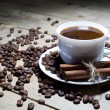 Cup of Coffee with Cinnamon and Coffee Beans on Wooden Table — Stock Photo #68933891