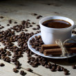 White Coffee Cup and Saucer with Cinnamon and Coffee Beans on Wooden Table — Stock Photo #68933985