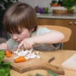 Left-Handed Boy Cutting Carrot on a Wooden Board Very Carefully in the Kitchen — Stock Photo #69905421