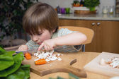 Left-Handed Boy Cutting Carrot on a Wooden Board Very Carefully in the Kitchen — Stock Photo