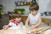 Cute Little Boy Showing His Twin Brother How to Flatten Dough at the Kitchen Table — Stock Photo