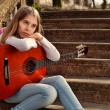 Pensive Teenage Girl Holding a Guitar in Her Lap Against Old Stone Stairs — Stock Photo #71075883