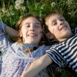 Smiling Children Lying on the Grass With Arms Outstretched  and Enjoying Sunny Spring Day — Stock Photo #73610479