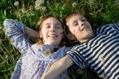 Smiling Children Lying on the Grass With Arms Outstretched  and Enjoying Sunny Spring Day — Stock Photo